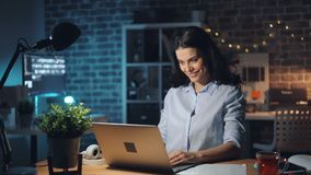 Happy businesswoman working in office late at night using computer smiling. Happy businesswoman attractive girl is working in office late at night using computer stock video footage