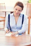 Happy businesswoman working outdoors on financial report. On sunny day, outside corporate office. Positive face expressions, emotions royalty free stock photo