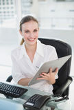 Happy businesswoman writing on clipboard sitting at desk Stock Photos
