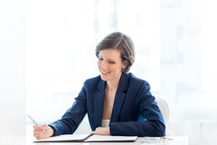 Happy Businesswoman Writing financial report at her Table Royalty Free Stock Photos