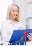 Happy businesswoman writing to clipboard in office. Education, business and people concept - happy businesswoman or student with clipboard and growing graph Stock Images