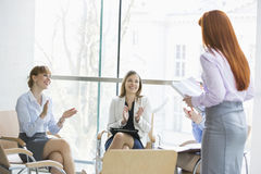 Happy businesswomen clapping for colleague after presentation in office Stock Photos