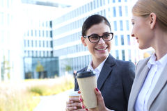 Happy businesswomen conversing while holding disposable cups outdoors Stock Images