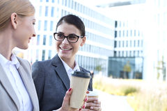 Happy businesswomen conversing while holding disposable cups outdoors Stock Photo