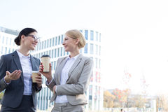 Happy businesswomen conversing while holding disposable cups outside office building Royalty Free Stock Images