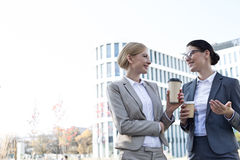 Happy businesswomen conversing while holding disposable cups outside office building Stock Photo