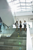 Happy businesswomen conversing while moving down steps in office stock photography
