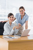 Happy businesswomen at desk smiling at camera Royalty Free Stock Images