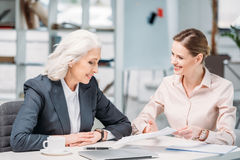 Happy businesswomen discussing business project on meeting in office royalty free stock photos