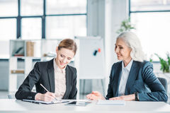 Happy businesswomen discussing business project on meeting in office. Two happy businesswomen discussing business project on meeting in office Stock Photography