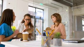 Happy businesswomen eating take out food at office. Business lunch and people concept - happy businesswomen eating take out food at office stock video