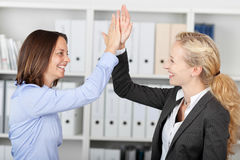 Happy Businesswomen Fiving High Five. Side view of happy businesswomen fiving high five in office royalty free stock photography