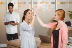 Happy businesswomen giving high five in office Stock Images