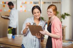 Happy businesswomen looking at clipboard in office Stock Images