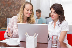 Happy businesswomen looking at computer screen together Stock Photos