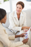 Happy businesswomen meeting to go over charts on the couch Royalty Free Stock Photography