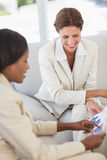 Happy businesswomen meeting to go over figures on the couch Royalty Free Stock Image