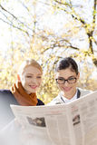 Happy businesswomen reading newspaper at park Stock Photos