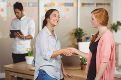Happy businesswomen shaking hands in office Royalty Free Stock Photography
