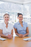 Happy businesswomen sitting side by side Stock Photos