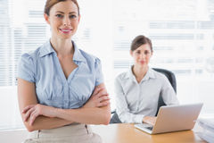 Happy businesswomen smiling at camera at their desk Stock Photos