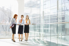 Happy businesswomen standing against glass wall in office Stock Photography