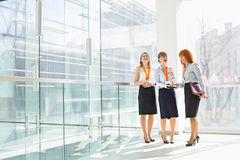 Happy businesswomen standing against glass wall in office royalty free stock photography