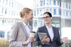 Happy businesswomen with tablet PC and disposable cup conversing outside office building Stock Photo