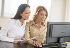 Happy Businesswomen Using Computer In Office Stock Images