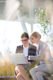 Happy businesswomen using laptop together on sunny day Stock Photos