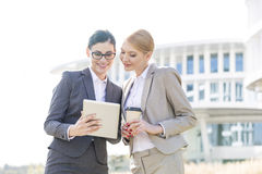 Happy businesswomen using tablet PC outside office building Royalty Free Stock Photography