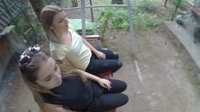 Happy businesswomen in vacation talking and swinging on swing outdoor in nature -. Happy businesswomen in vacation talking and swinging on swing outdoor in stock video