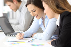 Happy businesswomen working together. Close up of two happy businesswomen working together at office Stock Images