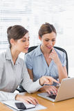 Happy businesswomen working together on a laptop. At desk in office Royalty Free Stock Photography