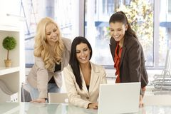 Happy businesswomen working together at office. Happy businesswomen working together on laptop computer at office, smiling Royalty Free Stock Photography