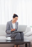 Happy busineswoman sitting on sofa using laptop Royalty Free Stock Images