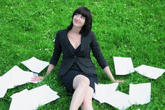 Happy busness woman. The happy business woman having a rest on a grass in an environment documents Royalty Free Stock Photography