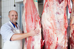 Happy butcher close to cow carcasses Royalty Free Stock Photos