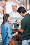 Happy Butcher With Couple Using Digital Tablet Royalty Free Stock Photo