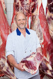 Happy butcher holding a freshly cut piece of beef Royalty Free Stock Photography