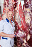 Happy butcher holding a knife near a cow carcass Stock Images