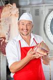 Happy Butcher Holding Meat In Shop Royalty Free Stock Photography