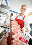 Happy Butcher Showing Meat Tray In Store Royalty Free Stock Photos