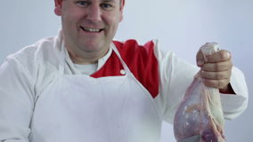 Happy butcher with turkey leg. Professional butcher preparing fresh turkey meat for cooking dishes and freezing in refrigerator for later use. Wide shots and stock video footage