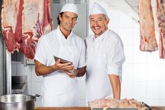 Happy Butchers With Digital Tablet At Counter Stock Image