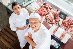 Happy Butchers Standing At Butchery Counter Stock Photography