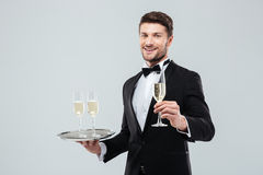 Happy butler in tuxedo holding tray and glass of champagne Stock Photos