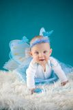 Happy butterfly. Cute baby girl on blue background Stock Photo