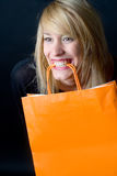 Happy buyer. Woman biting onto an orange paper bag with empty space, ready to place any text Royalty Free Stock Photos