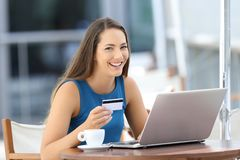 Happy buyer holding a credit card looking at you. Happy buyer using a laptop holding a credit card and looking at you sitting in a bar terrace Royalty Free Stock Images